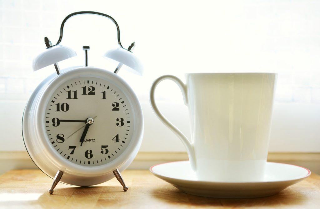 Achtsame Morgenroutine - Wecker und Kaffeetasse