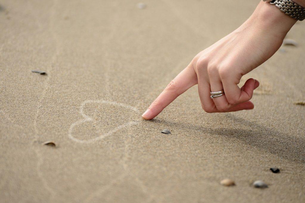 Selbstliebe Mantras für Mamas - Hand malt Herz in den Sand